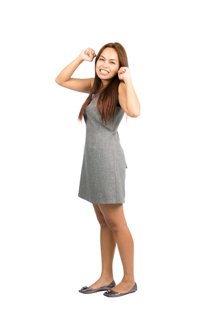 gritting: Teeth clenched Asian woman in gray dress with light brown hair, balled fists, looking at camera throwing immature temper tantrum, fed up, annoyed, irritated.