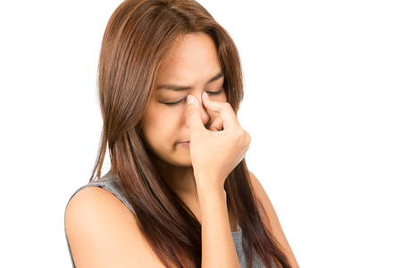 Portrait of suffering Asian woman, light brown hair in sleeveless gray dress pinching bridge of nose in pain and discomfort from sinus congestion, splitting headache.