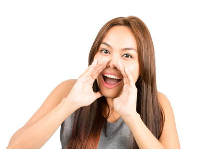 sleeveless top: Portrait of good looking Asian girl, sleeveless top, light brown hair shouting announcement looking at camera, hands cupped around mouth amplifying sound.