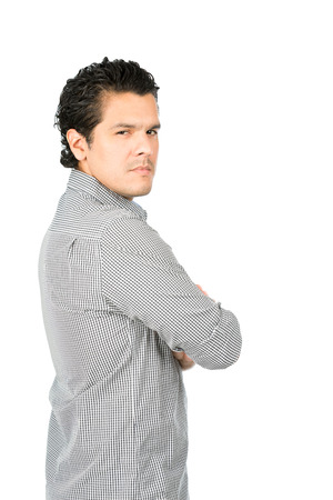 latino man: Rear view of angry, disappointed latino man wearning casual clothes arms crossed looking behind at camera over his shoulder showing judgmental, critical, unhappy, displeased attitude. Vertical half Stock Photo