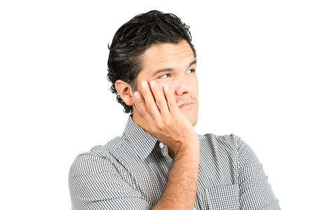 latino man: Portrait of serious, worried latino man in casual clothes, cupping chin, head in hand looking away to side at blank copy space, imaginary inserted product showing angst, perplexed thinking