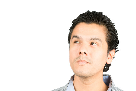 expressionless: Portrait of a pensive, reserved, handsome hispanic man looking up to the side at blank copy space or product with serious facial expression showing deep thought, curiosity, interest, wonder Stock Photo