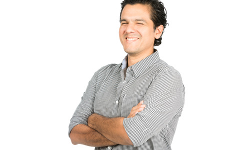 good attitude: A good looking latino male wearing collared button down shirt laughing with arms crossed looking at the camera showing easy going, warm, friendly, positive, jovial attitude and big smile.  Stock Photo