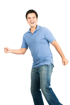 jovial: A pleasantly surprised latino male dressed casually in blue jeans, shirt with big smile is caught off-guard by something walking mid-stride mid-step Stock Photo