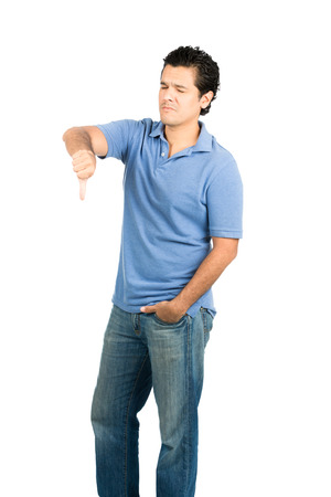 disapproving: Hispanic male in casual clothes with eyes closed, hand in pockeet and frowning facial expression, gesturing thumb down showing disapproval, disappointment, failure