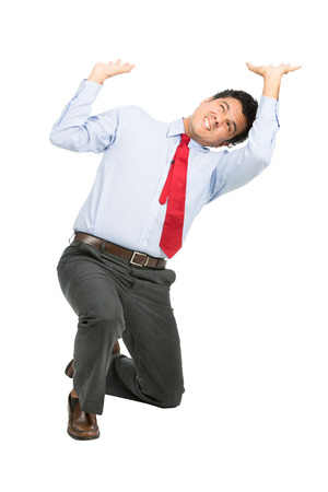 positions: A stressed latino businessman in business clothes on knee using arms pushing up, resisting against crushing imaginary weight, object under heavy stress, feeling pressure. Isolated on white background Stock Photo