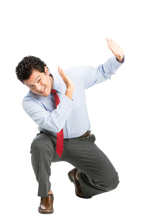 An intimidated latino man office worker in business attire crouching putting hands to shield in self defense, protecting against verbal, physical abuse assault off-screen. Workplace violence