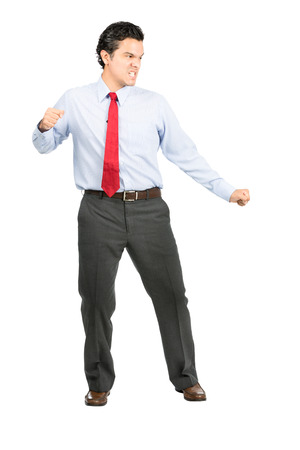 standing businessman: An angry, aggressive hispanic male office worker in formal dress suit, red tie, fierce facial expression strikes a martial arts stance looking away to side fighting imaginary opponent. Full