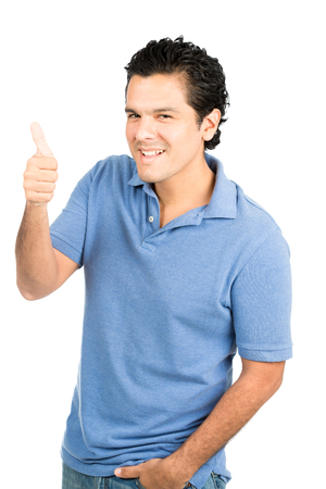 Handsome hispanic male wearing blue shirt with big smile, right thumb up sign expressing satisfaction, job well done, approval, positivity