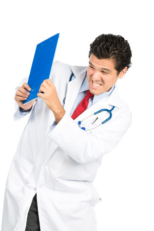 A latino doctor with clenched teeth, under stress, protecting in a defensive posture under attack blocking an assault with clipboard as shield.