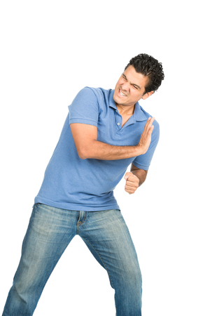 A struggling latino man casual clothes driving back, defending, forcing, pushing against imaginary insert object coming from side using body weight