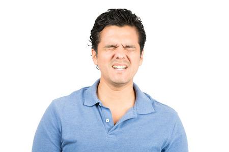 ojos tristes: Apuesto hombre hispano en camisa de cuello azul los ojos cerrados, haciendo una mueca con expresión de dolor facial de sufrimiento, el dolor, el dolor y la agonía Foto de archivo