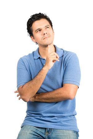 Een knappe Spaans mannetje in casual kleding met gekruiste armen, vingers onder de kin, zich afvragend, concentreren, het bedenken van een gedachte of geheugen zoeken en weg. Verticaal
