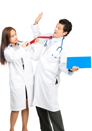 surrender: An angry female Asian doctor physically attacks hispanic male colleague, frustrated, pulling his tie, him scared, recoiling and surrendering in exaggerated terror. Vertical Stock Photo