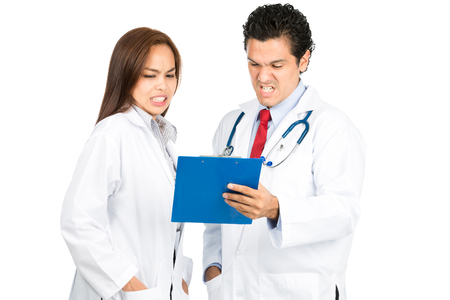 horrified: A diverse male, female, hispanic, Asian team of doctors reviewing medical charts together grimacing with shocked, pained reaction, horrified at bad diagnosis. Horizontal Stock Photo
