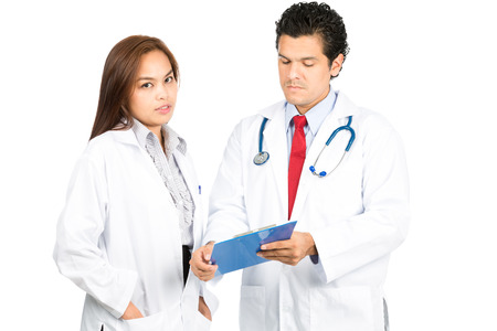 studious: A diverse latino male, asian female team of doctors, one looking at camera while other is listening, reviewing, discussing medical charts diagnosis with serious, studious expressions. Horizontal