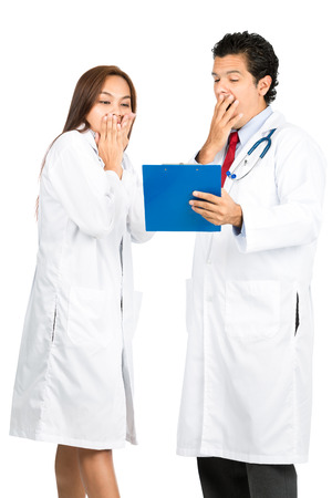 horrified: A diverse male, female team of doctors covering mouth showing surprised, horrified, shocked reaction seeing patient bad news diagnosis on clipboard medical records. V Stock Photo