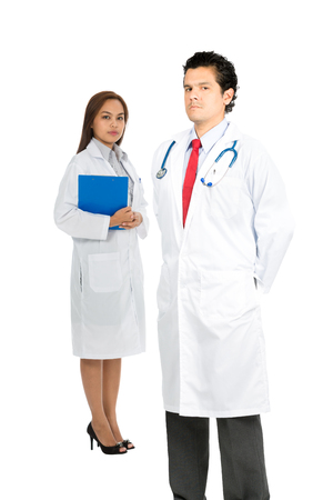 foreground focus: A confident latino male, asian female multi-ethnic doctors diverse team, shows compassion and caring with serious expression. Focus on foreground Vertical