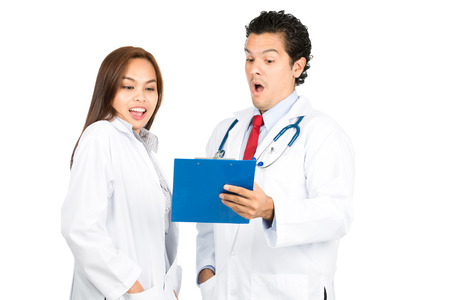 exaggerated: A diverse male, female team of doctors shows exaggerated reaction mixed surprised, shocked, pleased examining patient diagnosis together on clipboard medical records. Horizontal Stock Photo