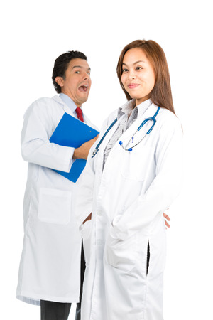 foreground focus: A pretty Asian female, hispanic male doctors having fun joking around making silly, goofy, funny facial expressions showing sense of humor. Focus on foreground