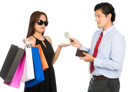 preguntando: A shopaholic superficial estilo femenino asiático con sus bolsas de tiendas por departamento sostiene la mano para recibir el dinero de compras de su marido reacios H