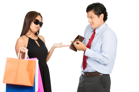 woman standing: A greedy shopaholic gold digger stylish Asian wife demanding money for shopping from her poor sympathetic husband showing his empty wallet with no money. Half H Stock Photo