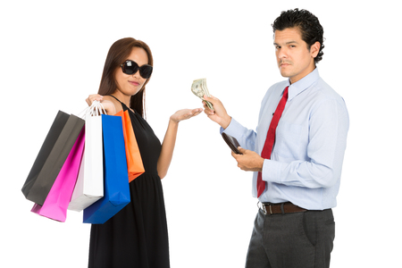 accepts: A trendy Asian woman shopaholic with black dress, sunglasses and department store bags accepts money from her wealthy husband looking at camera. H