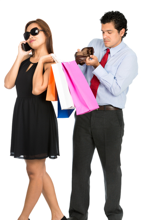 A broke abused hispanic husband shows an empty wallet to a detached, callous, aloof, shopaholic, gold digger wife with her back turned talking on her cell phone concerned more about shopping. V