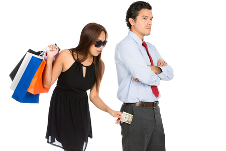 secretly: A greedy woman shopaholic with department store shopping bags secretly removing money unnoticed from her pushover husband pants pocket while standing and looking away. H