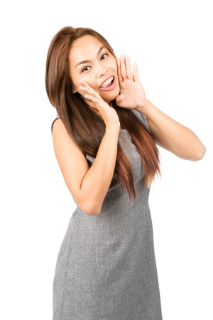 asian adult: Profile of cute, happy Asian woman, sleeveless gray dress, light brown hair looking at camera, shouting announcement cupped hands around mouth. Thai national Chinese origin. Half length Vertical