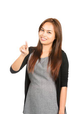 Lovely Asian woman in casual clothes with light brown hair, index finger pressing, interacting with imaginary button or touchscreen interface looking at camera. Thai national Chinese origin. Vertical