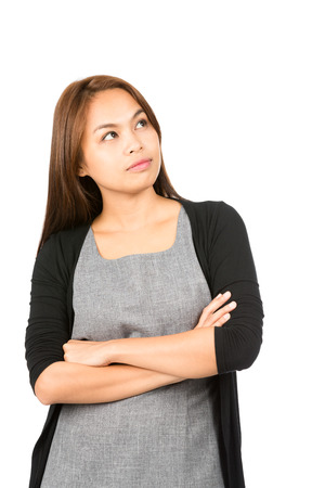 young woman face: A lovely, modern Asian woman with serious, curious facial expression, arms crossed thinking, looking up to side at copy space showing interest, wonder. Thai national of Chinese origin. Vertical Half