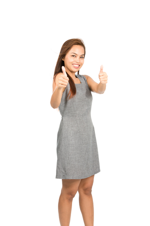 two thumbs up: A good looking Asian woman, light brown hair in gray sleeveless dress enthusiasticly approving with two thumbs up giving blessing or compliment of good job or product. Thai national of Chinese origin Stock Photo