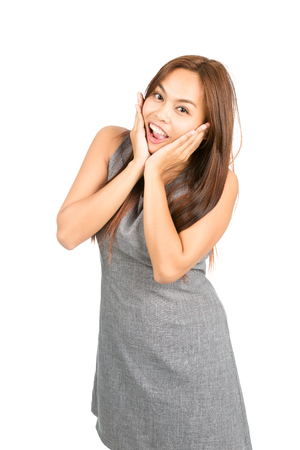 euphoria: A happy, surprised Asian woman, light brown hair in gray dress cupping face, head in hands shows happy euphoria, beaming reaction to good news or information. Thai national of Chinese origin. Half
