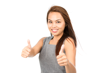 sleeveless dress: Cute smiling Asian girl with light brown hair in gray sleeveless dress looks at camera holding both thumbs up showing approval, good quality product or job well done. Thai national of Chinese origin