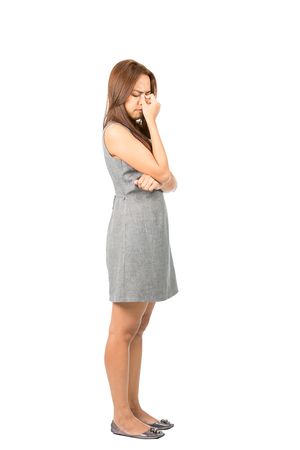 sufferer: Profile of frowning migraine sufferer Asian woman in sleeveless gray dress holding bridge of nose suffereing from sinus congestion or headache. Thai national of Chinese origin. Full length