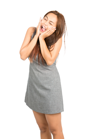 high angle: High angle view of scared, terrified Asian girl in casual sleeveless gray dress, head in hands, cupped chin screaming with eyes closed looking up. Thai national of Chinese origin. Vertical Stock Photo
