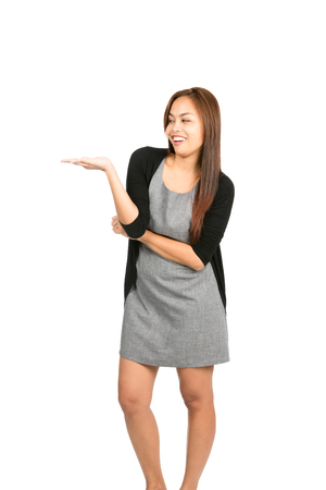 asian adult: A cute, cheerful Asian female with big smile wearing a short dress, sweater holding hand out displaying an imaginary inserted product in flat open palm up. Thai national of Chinese origin. Vertical