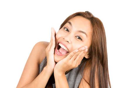 reacting: Portrait of blissful, euphoric Asian woman, light brown hair in sleeveless clothes, face cupped, head in hands reacting positively to happy news or information. Thai national of Chinese origin Stock Photo