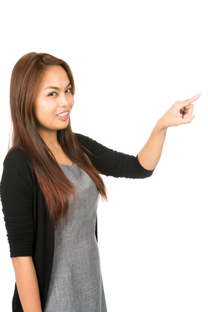 half length: Side profile of gorgeous Asian woman in black sweater with light brown hair, arm extended index finger pressing imaginary button looking at camera. Thai national Chinese origin. Half length vertical Stock Photo