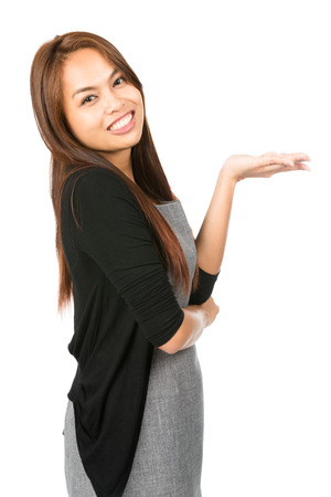 palmier: Side profile of Asian woman in gray dress, black sweater leaning back, looking at camera holding hand flat out displaying imaginary inserted product on open palm. Thai national of Chinese origin Half