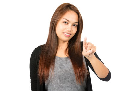 Lovely Asian woman in black sweater with light brown hair with raised index finger pointing at camera or pressing imaginary touchscreen interface. Thai national of Chinese origin. Horizontal