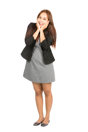 chin on hands: A happy, ecstatic Asian businesswoman in black business jacket, gray dress cupping chin, head in hands showing overjoyed reaction to great news. Thai national of Chinese origin. Full