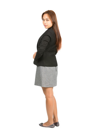expressionless: Rear view of serious Asian businesswoman in black business jacket, gray dress looking back over her shoulder at camera showing professional attitude, demeanor. Thai national of Chinese origin. Full