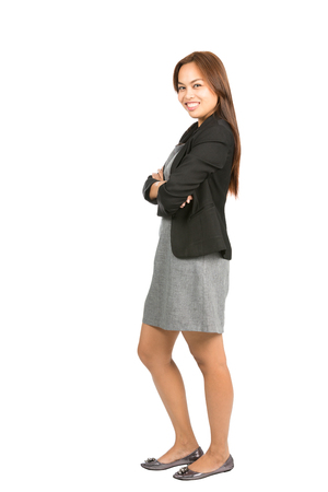 warmly: Side profile of engaging, charming, natural Asian businesswoman in casual black jacket, gray dress, arms crossed warmly smiling at camera. Thai national of Chinese origin. Full