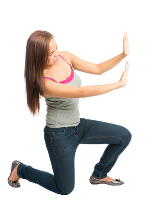 Struggling Asian woman in casual clothes, kneeling with extended arms, defending, forcing, pushing, fighting against imaginary insert object encroaching from side Stock Photo
