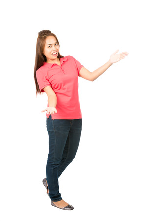 Profile of lovely Asian female, casually dressed, arms extended out to side, body language presenting or displaying an imaginary inserted product in copy space while looking at camera. Full Stockfoto