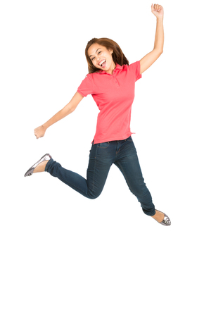 spread legs: Asian woman celebrating in mid-air jumping with exaggerated smile, arms legs extended, fist raised showing extreme happiness, ecstatic, overjoyed emotion and laughing Stock Photo
