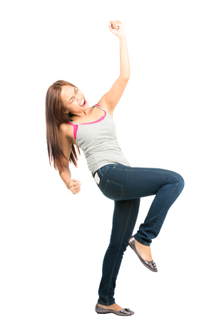 Ecstatic, good looking Asian woman in casual clothes jeans and tank top, eyes closed, screaming, celebrating and winning by raising fist thrust into the air while facing away Stock Photo