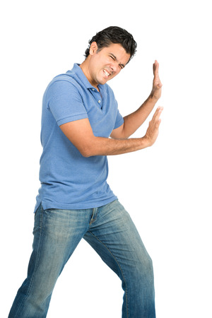 A strong, struggling latino male in casual blue clothes with extended arms is defending, forcing, pushing against imaginary insert object encroaching from side while looking away from the camera Stock Photo